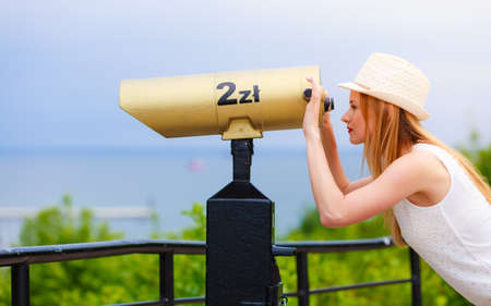 Traveling, adventure, vacation concept. Woman tourist wearing sun hat looking through telescope into the distance