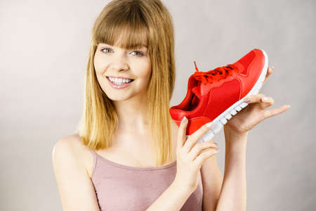 Happy sporty smiling woman presenting sportswear trainers red shoes, comfortable footwear perfect for workout and training.