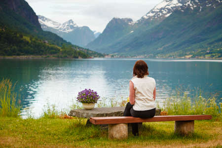 Travel concept. Mature tourist woman sitting on bench on sea shore looking at fjords beautiful landscape, in Olden village, Sogn og Fjordane county Norway. Stock Photo
