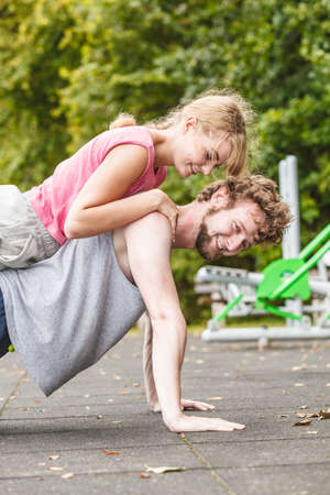 Active young man and woman exercising doing push ups. Muscular strong guy and girl in training suit working out at outdoor gym. Sport fitness and healthy lifestyle concept.