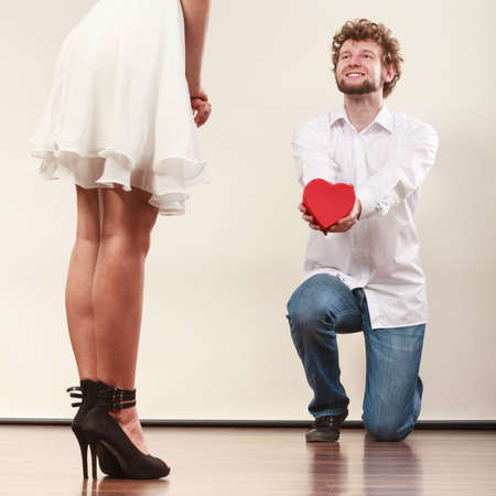 Man guy holding heart shaped present gift box for hot sexy woman girl in high heels. Valentine day love concept.
