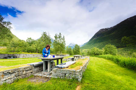 Traveler woman have lunch on nature. Picnic site table and benches with view at norwegian mountains, Scandinavia Europe. Imagens