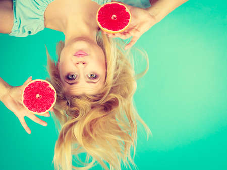 Healthy diet, refreshing food full of vitamins. Happy crazy woman holding sweet delicious citrus fruit, red grapefruit having windblown hair.