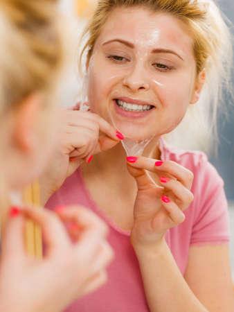 顔の乾燥肌とボディケア、家庭での顔色治療。顔からジェルの皮を剥がす女性