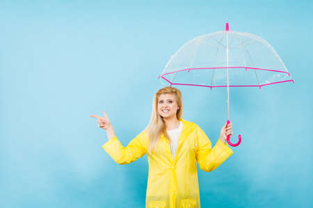 Blonde woman wearing yellow raincoat holding transparent umbrella checking weather if it is raining pointing with finger at copyspace. Stock fotó - 96193321