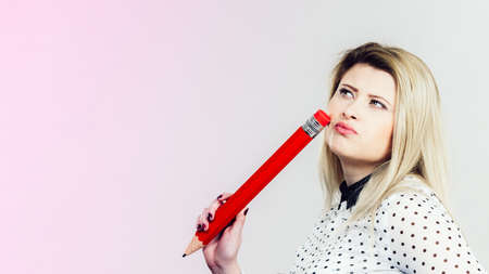 Woman hand holding big pencil. Studio shot on light background with copyspace.