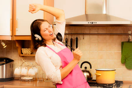 Cooking preparing and making food concept. Modern beauty woman housewife cook chef wearing pink apron listening music on earphones singing and dancing in kitchen.