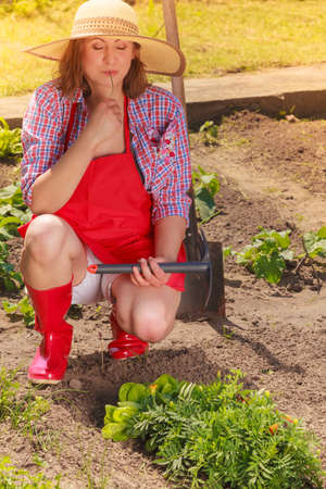 Mature woman wearing hat red rubber boots with gardening tool working in her backyard garden outdoor Фото со стока