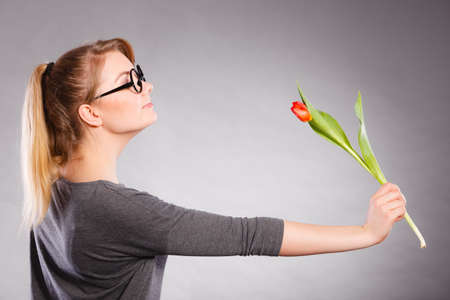 Peace and content. Beauty adorable girl smelling beautiful spring flower. Peaceful enjoyable woman with red green tulip. Lady smell nature. Stok Fotoğraf