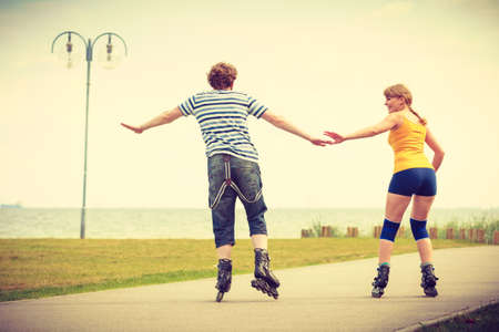 Holidays, active people and friendship concept. Young fit couple on roller skates riding outdoors on sea shore, woman and man rollerblading together on the promenade Stockfoto