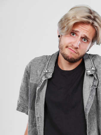 Confusion, questionable. Standing blonde man wearing grey shirt being confused, studio shot white background.