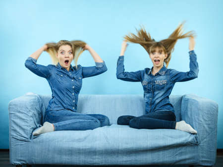 Two shocked women wearing jeans shirts having windblown blonde hair. Blue background. Stock Photo