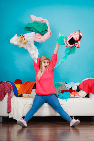 Clothing dilemmas concept. Shocked woman sitting on messy couch throwing clothes above head. Stock Photo