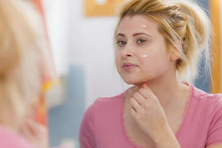 Facial dry skin and body care, complexion treatment at home concept. Young woman having gel peel off mask on her face.