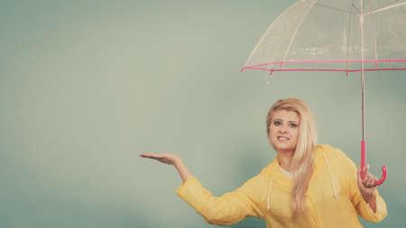 Blonde woman wearing yellow raincoat holding transparent umbrella checking weather if it is raining. Stock fotó - 114656765