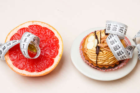 Concept of making choice: healthy low-calorie or unhealthy high-calorie food, slimming or fattening. Grapefruit and cake cupcake with measuring tape Banco de Imagens