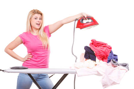 Household duties, taking care of house concept. Woman standing behind board holding iron having pile of clothes to ironing