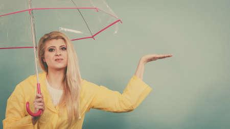 Blonde woman wearing yellow raincoat holding transparent umbrella checking weather if it is raining.