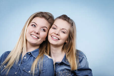 Friendship, human relations concept. Two happy women friends or sisters wearing jeans shirts pointing somewhere. Stock Photo