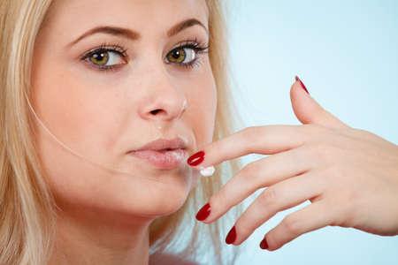 Diät, Bonbonversuchung, köstliches Nahrungsmittelkonzept. Frau, die Schlagsahne vom Finger leckt oder Lippenbalsam auf die trockenen Lippen aufträgt und ihre roten Nägel darstellt