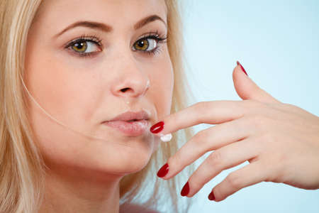 Diet, sweets temptation, delicious food concept. Woman licking whipped cream from finger or applying lip balm to dry lips, presenting her red nails Stock Photo - 97415951