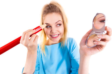 Funny silly woman trying to paint her eyebrows using big huge oversized regular student pencil. Make up fun concept. Standard-Bild