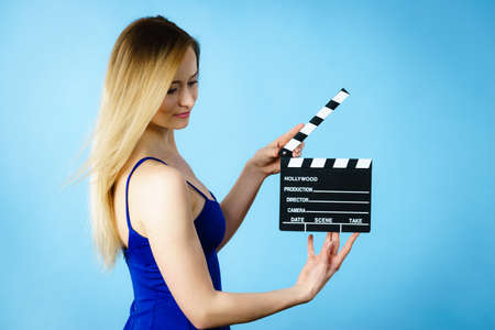 Woman holding professional film slate, movie clapper board. Hollywood production objects concept. Studio shot on blue background.