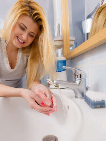 Woman washing her hands in sink to get rid of dirt. Personal hygiene concept. 版權商用圖片