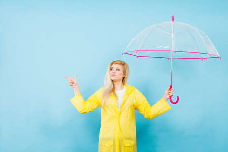 Blonde woman wearing yellow raincoat holding transparent umbrella checking weather if it is raining pointing with finger at copyspace. Stock fotó - 97583704