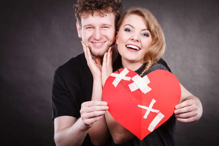 Heal love concept. Couple woman and man holding two halves of broken heart fixed with plaster bandage going to be joined in one.  Stockfoto
