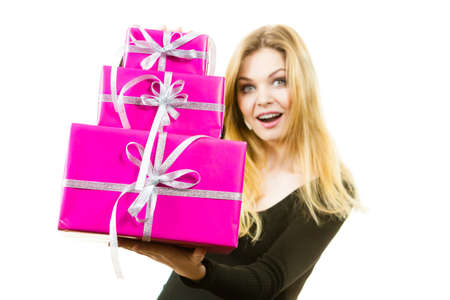 Woman being shocked by amount of gifts she received. Female having weirdly surprised face expression holding big stack of presents.