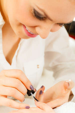 Closeup of beautician painting nails of female client. Woman in beauty spa salon doing manicure Stock Photo