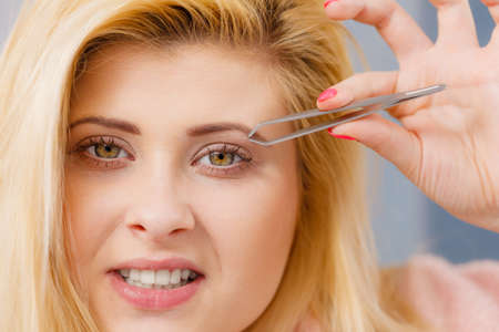 Woman plucking eyebrows depilating with tweezers closeup part of face. Girl tweezing removing her facial hairs..