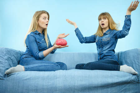 Friendship, human relations concept. Two women friends or sisters wearing jeans shirts, thinking about solving problem holding fake brain.
