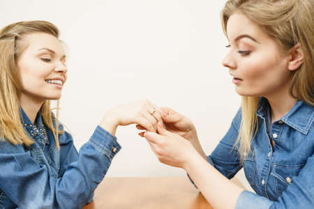 Woman showing her happy shocked female friend engagement ring sharing great news.