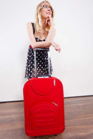 Concetto di vacanza itinerante. Elegante giovane donna in abito nero a pois che indossa una pesante borsa da viaggio rossa