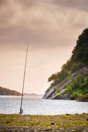 Fishing rod left alone on shore near lake and mountains. Cloudy scandinavian weather.