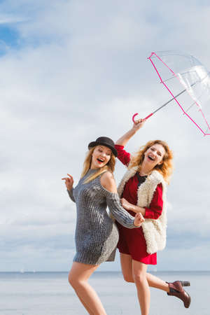 Two fashionable women wearing stylish outfits holding transparent umbrella spending their free time outdoor