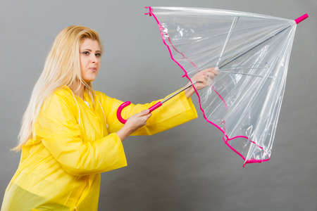 Rainy autumn day accessories ideas concept. Woman having serious face expression holding opening clear transparent umbrella fighting with wind.