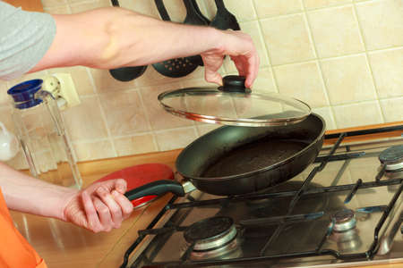 Closeup of human hand with heating frying fry pan on burning gas burner stove. Stock fotó