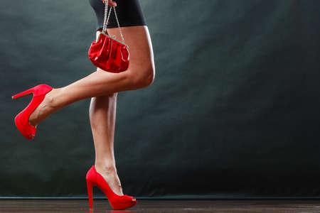 Celebration disco and evening fashion concept. Woman in black short dress red spiked shoes holding handbag bag, part of body female legs in high heels on party floor Stock Photo