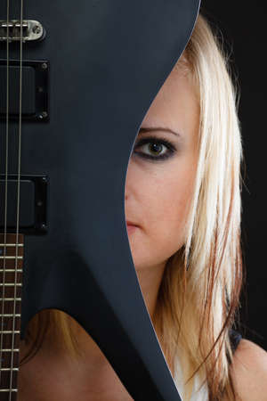 Music, singing concept. Blonde musically talented woman holding electric guitar on black background