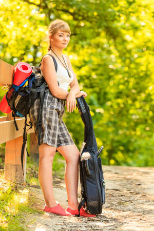 Adventure, tourism, enjoying summer time - young tourist woman with backpack hiking in forest trail