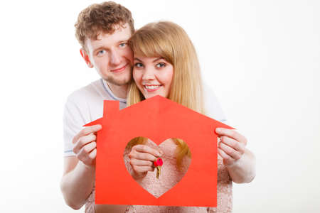 People, fresh start, real estate and love concept. Young enjoyable enamoured marriage holding red house with big heart and keys to their future. Stok Fotoğraf