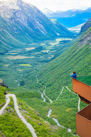 Travel concept. Tourist woman looking at Trolls Path Trollstigen or Trollstigveien winding scenic mountain road, taking picture with camera from viewing point, Norway Europe
