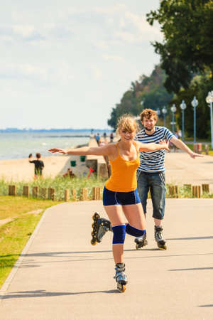 Holidays, active people and friendship concept. Young fit couple on roller skates riding outdoors on sea coast, woman and man rollerblading together on the promenade Stock Photo
