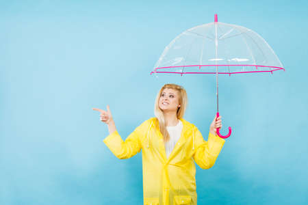 Blonde woman wearing yellow raincoat holding transparent umbrella checking weather if it is raining pointing with finger at copyspace. Stock Photo