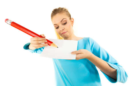Teenage woman writing some notes on piece of paper using big oversized pencil.