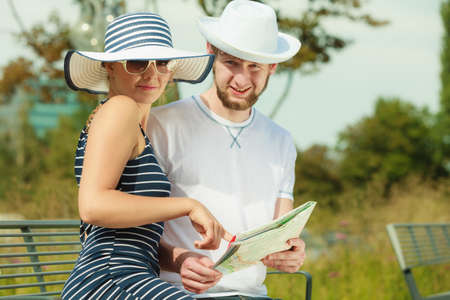 Summer travel concept. Young tourist couple on vacation sitting on city bench looking up directions on map