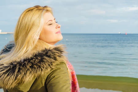 Leisure, spending free time outside, healthy walks concept. Woman wearing warm jacket relaxing on beach near sea, cold sunny day, back view Stockfoto
